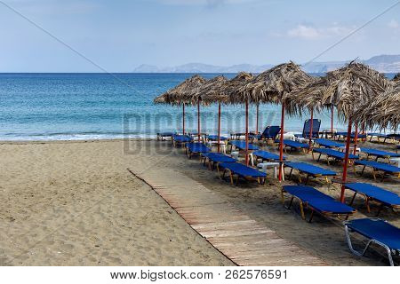 Deserted, sandy beach with sunbeds and umbrellas on an autumn day (Sitia, Crete, Greece) stock photo