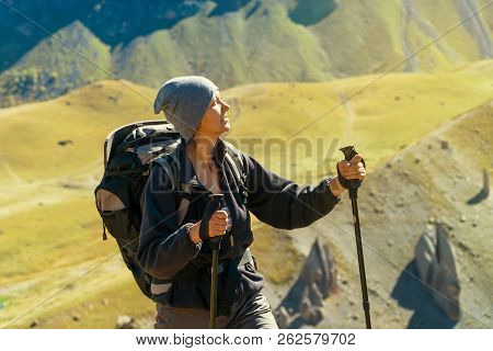 Hiker woman with backpack walking the edge of the canyon. Enjoying nature vacation travel adventure at Caucasus mountains. stock photo