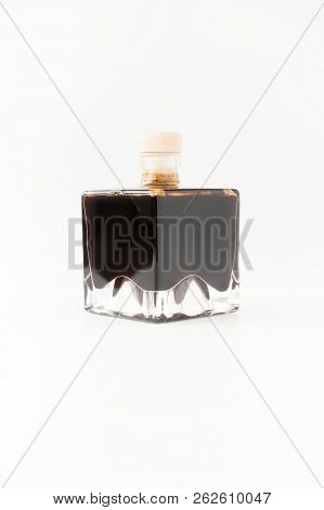 Balsamic Vinegar of Modena in square stackable glass bottles isolated on white background. stock photo