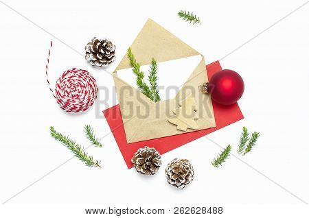 Christmas composition. Envelope with blank white paper, fir branches, cones, red ball, twine for gift on white background Flat lay top view copy space, square. Christmas winter decoration, New Year stock photo