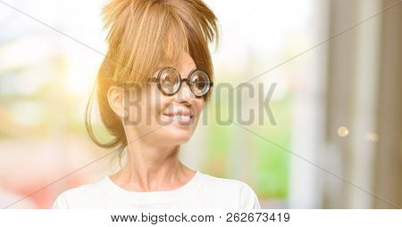 Crazy middle age woman wearing silly glasses thinking and looking up expressing doubt and wonder stock photo
