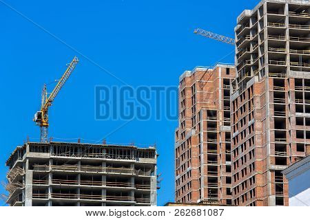 The under construction much floor monolithic building with brick filling, the bottom view against the background of the sky and cranes. stock photo