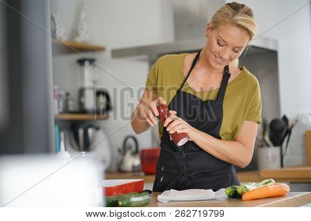 40-year-old woman cooking in home kitchen  stock photo