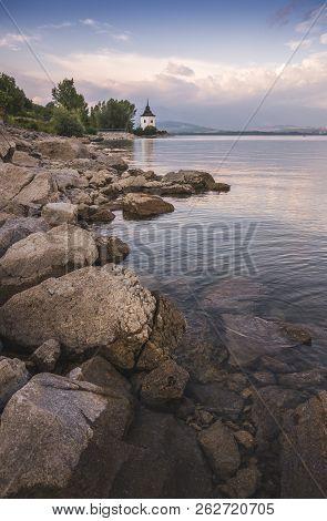 Church on Rocky Beach of Liptovska Mara Lake in Slovakia stock photo
