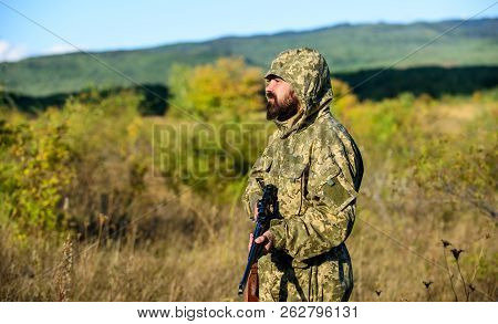 Hunting season. Man bearded hunter with rifle nature background. Experience and practice lends success hunting. How turn hunting into hobby. Guy hunting nature environment. Masculine hobby activity stock photo