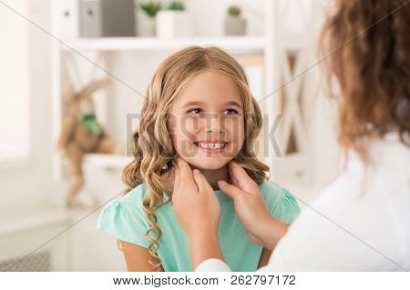 Perfect tonsils. Positive girl staring at female doctor who checking her tonsils stock photo
