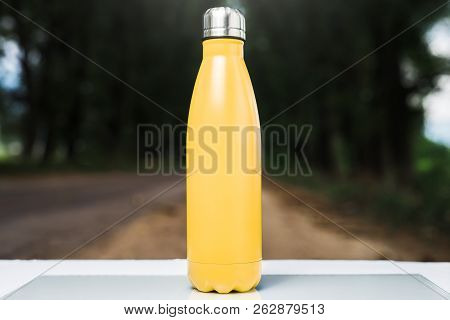 Stainless thermos water bottle on white table, outdoor. Yellow color. stock photo