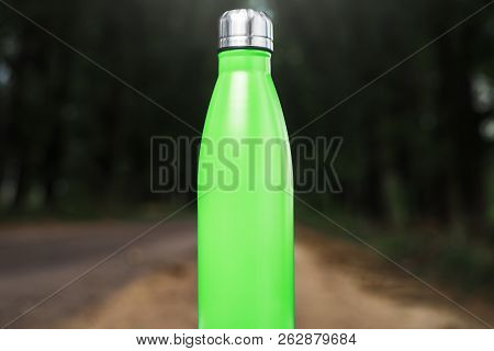 Stainless thermos water bottle on white table, outdoor. Light green color. stock photo