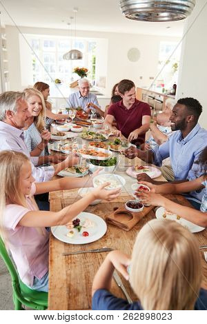 Group Of Multi-Generation Family And Friends Sitting Around Table And Enjoying Meal stock photo