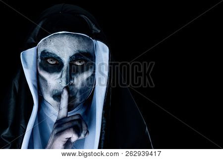 closeup of a frightening evil nun, wearing a typical black and white habit, asking for silence, against a black background with a blank space on the right stock photo