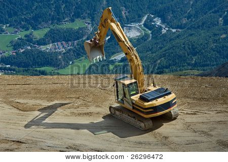 excavator at a construction high up in the mountains stock photo