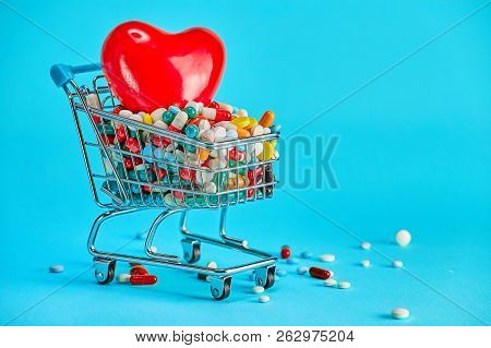 Colorful pills with red heart in shopping cart on blue background. The concept: trade in medicines, pharmacies. stock photo