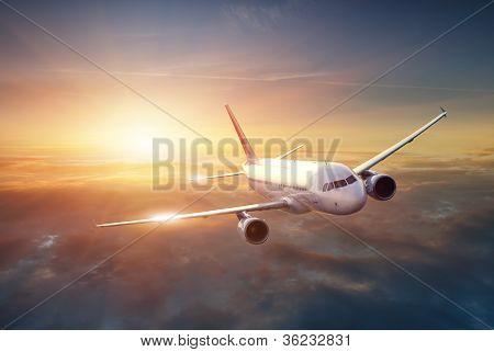 Avion dans le ciel au coucher du soleil