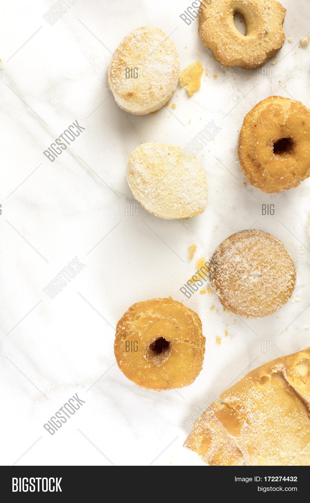 A photo of mantecados, polvorones and other traditional Spanish cookies, shot from above on a marble texture, with a place for text