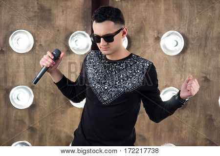 Male singer of rock or pop music dressed in black and sunglasses with microphone performs on scene with lightening projectors on background stock photo