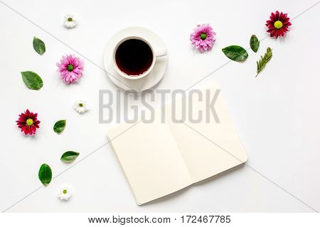 Froral flat lay with cup of coffee and craft notepaper on white background top view mockup stock photo