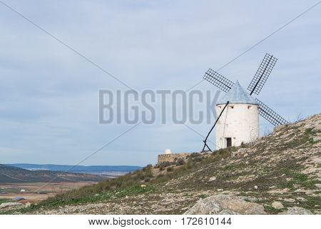 White old windmill on the hill near Consuegra (Castilla La Mancha Spain) a symbol of region and journeys of Don Quixote (Alonso Quijano) on cloudy day. stock photo