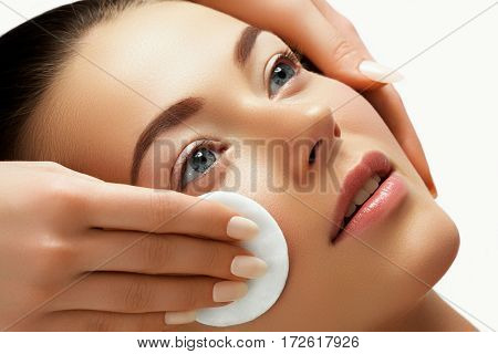 Portrait of happy smiling beautiful young woman cleaning skin by cotton pad at spa salon. Beautiful face of a young woman. Woman beauty face portrait with healthy skin. Natural beauty concept stock photo