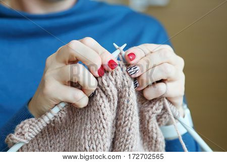 Hands of knitting woman in blue dress, close up view, noface stock photo
