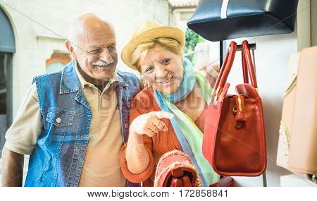 Senior couple shopping at fashion bag store with wife pointing showcase to husband - Active elderly concept with mature man and woman having fun in city - Happy retired people moments on vivid colors stock photo