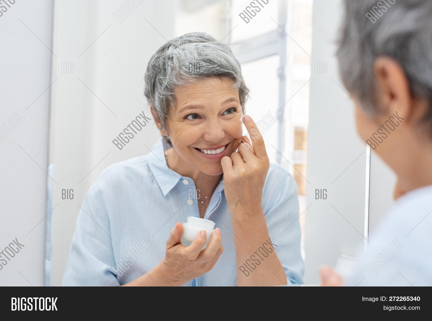 50s,aging process,aging skin,anti,anti aging,anti aging cream,apply,applying,bathroom,beauty,beauty treatment,beauty woman,care,caucasian,clean,cleansing,complexion,cosmetic,cosmetology,cream,dermatology,elderly woman,face,facial,finger,hand,happy,health,healthy,looking at mirror,mature,middle aged woman,mirror,moisturizer,moisturizer cream,moisturizing,morning,routine,senior,senior woman,seniors,skin,skin care,skincare,toothy smile,treatment,wrinkle,wrinkled,wrinkles