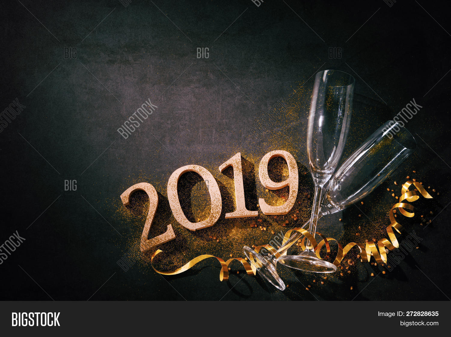 New Years Eve or Birthday celebration. Two champagne glasses with numbers 2019 and streamers on dark