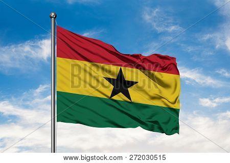 Flag of Ghana waving in the wind against white cloudy blue sky. Ghanaian flag. stock photo