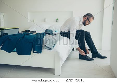 Close up side profile photo of sitting on bed bedroom  attractive handsome getting putting on shoes wearing specs his him he perfect looking in formalwear stock photo