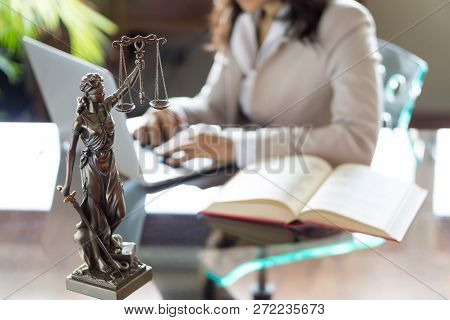 Lawyer office. Statue of Justice with scales and lawyer working stock photo
