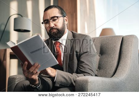 Bearded smart advocate wearing red tie reading administrative law stock photo
