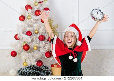 Girl kid santa hat costume with clock excited happy face counting time to new year. Last minute new years eve plans that are actually lot of fun. Last minute till midnight. New year countdown stock photo