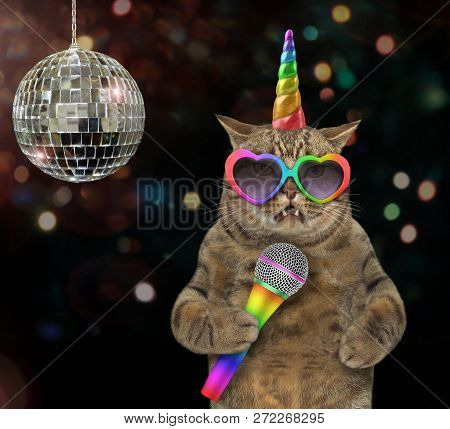 The cat unicorn in rainbow glasses is singing a song at the stage near a mirror ball. stock photo