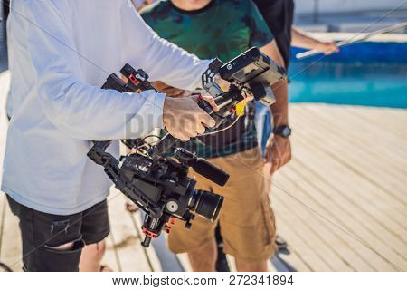 Professional steadicam operator uses a 3-axis camera stabilizer system on a commercial production set stock photo
