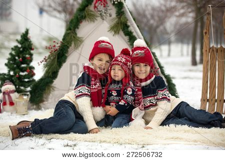Happy family with kids, having fun outdoor in the snow on Christmas, playing with sledge, teepee and christmas decoration stock photo