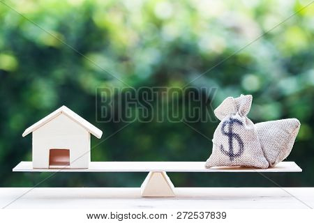 Home loan, mortgages, debt, savings money for home buying concept : Balance a money bag and small residential, house model on table against green nature background. Exchange of finances and houses. stock photo