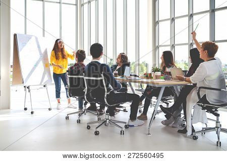 Young asian creative hipster female leader standing and making presentation at modern office happy talking marketing idea with team. Casual asian people business meeting workshop soft tone concept. stock photo