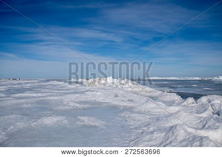 Frozen Baltic sea coastline covered with stack of ice floes and blue sky stock photo