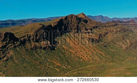 aerial drone image of beautiful stunning landscape view off the Degollada de La Yegua viewpoint with cliff rock peaks and valley with a curvy road on a sunny day stock photo