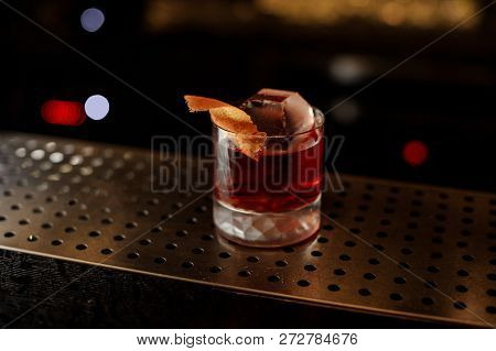 Glass of a Boulevardier cocktail with big ice cube and orange zest on the steel wooden bar counter on the blurred background stock photo