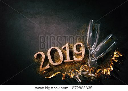 New Years Eve or Birthday celebration. Two champagne glasses with numbers 2019 and streamers on dark background stock photo