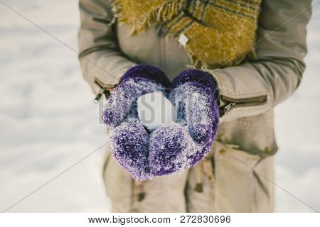 Portrait of a beautiful young Caucasian woman in a knitted hat and scarf standing on a winter background with snow smile and happiness purple gloves sculpt a snowball stock photo