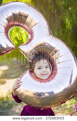 Cute Baby Girl Playing With Number Three Mylar Balloon Outdoors. stock photo