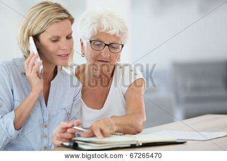 Homehelp booking medical appointment for elderly woman stock photo