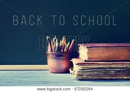 some pencils in a pot, some old books on a blue school desk, and the text back to school written on