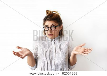 Indoor shot of emotional funny young woman in eyeglasses and formal shirt looking confused and puzzled her arms out shrugs shoulders. Emotions facial expressions feelings body language