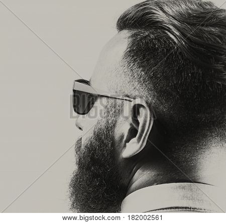Portrait of a bearded man in sunglasses with a stylish haircut. Black and white. stock photo