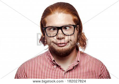 Carzy funny cross eyed bearded readhead businessman with red shirt and freckles and glasses looking at camera. studio shot isolated on white. stock photo