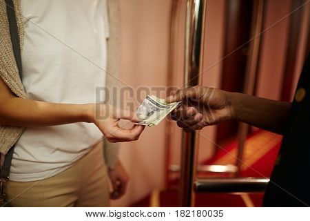 Hotel guest giving porter money for carrying her baggage stock photo