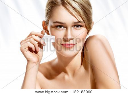 Gorgeous woman applying foundation on her face using makeup sponge. Beautiful woman face on white background. Perfect makeup stock photo
