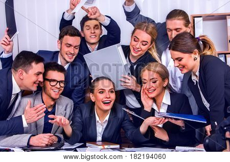 Business people office life of team people are happy with hand up sitting table and working papers . Cabinets with folders and jalousie background. stock photo